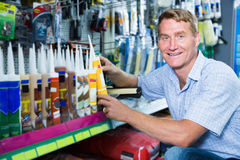 选择密封胶管的友好的人顾客在大型超级市场 免版税图库摄影
