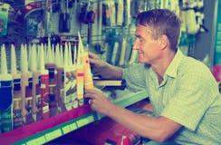 选择密封胶管的愉快的人顾客在大型超级市场 免版税库存图片