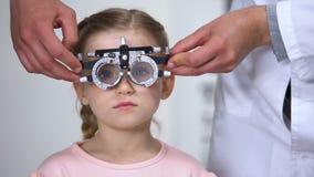 选择屈光率的眼科医生对女孩,使用光学设备 股票视频