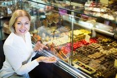选择巧克力和糖果店的妇女 免版税库存照片