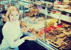 选择巧克力和糖果店的妇女 库存照片