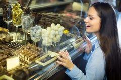 选择巧克力的微笑的女孩 免版税库存照片