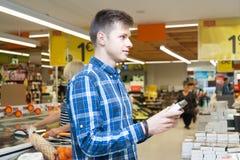 选择巧克力糖的一个年轻人在超级市场 库存图片