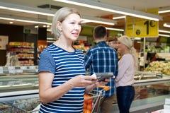 选择巧克力糖的成熟妇女在超级市场 免版税库存照片