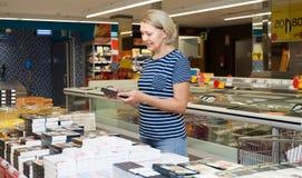 选择巧克力糖的成熟妇女在超级市场 免版税库存图片