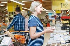 选择巧克力糖的成熟妇女在超级市场 库存照片