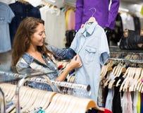 选择布料的妇女在商店 免版税库存照片