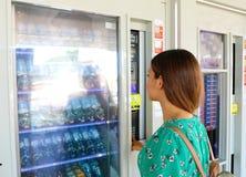 选择快餐或饮料的年轻女性背包徒步旅行者游人在自动售货机在威尼斯,意大利 有女孩的自动售货机 免版税库存照片
