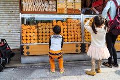 选择快餐的未认出的孩子在Nakamise Dori Sensoji寺庙商店地区fam 免版税图库摄影