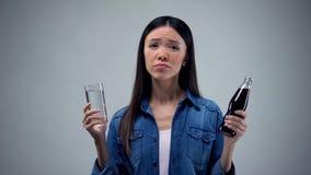 选择怎样的渴妇女喝在新鲜和泡沫腾涌的水,决定之间 免版税库存图片