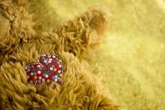 (选择性焦点)在一个玩具熊的被缝的逗人喜爱的红色心脏有金子闪烁背景 免版税库存照片