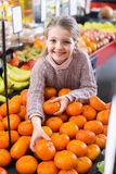 选择成熟蜜桔的小女孩 免版税图库摄影
