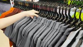 选择折扣衣裳的顾客的手在购物中心 搜寻或买便宜的棉花的人们在机架挂衣架的灰色T恤杉 免版税库存照片
