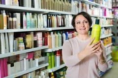 选择护发产品的快乐的正面迷人的妇女 免版税图库摄影