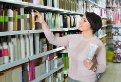 选择护发产品的愉快的妇女在商店 图库摄影
