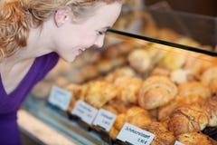 选择新月形面包的女性客户在面包店 免版税库存照片