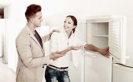 选择新的冰箱的赞赏的夫妇在大型超级市场 库存图片