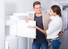 选择新的冰箱的年轻夫妇在大型超级市场 库存图片
