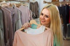 选择新的女衬衫的金发碧眼的女人 库存图片