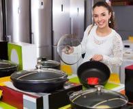 选择新的平底锅和罐的女孩在超级市场 免版税库存图片