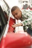 选择新的汽车的英俊的非洲人在经销权 免版税库存照片