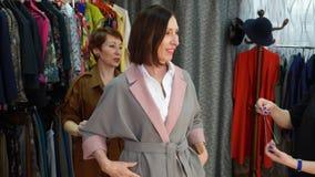 选择新的衣裳的妇女在时尚商店,当购物时 帮助的卖主选择衣裳和辅助部件为 影视素材