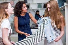 选择新的衣裳的年轻女朋友结合,评估,谈论礼服在衣物商店 库存图片