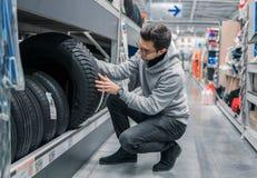 选择新的轮胎的聪明的男性顾客在超级市场 库存图片