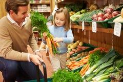 选择新鲜蔬菜的父亲和女儿在农厂商店 免版税图库摄影