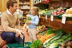 选择新鲜蔬菜的父亲和女儿在农厂商店 免版税库存图片