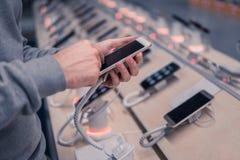 选择智能手机的年轻男性顾客 免版税库存图片