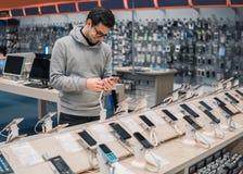 选择智能手机的愉快的男性顾客 免版税图库摄影