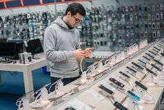 选择智能手机的聪明的男性顾客 免版税库存照片