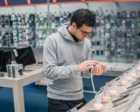 选择智能手机的聪明的男性顾客 免版税图库摄影