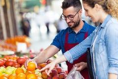 选择果子的一些类型的推销员帮助的顾客在fruitshop愈合 免版税库存照片