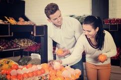 选择果子的夫妇在商店 免版税库存照片
