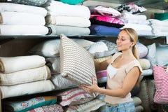 选择柔软的枕头的妇女顾客在家庭商店 免版税库存图片