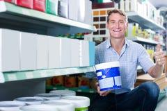 选择油漆桶的友好的人顾客在大型超级市场 免版税库存图片