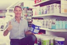 选择油漆的微笑的人顾客在大型超级市场用桶提 免版税库存图片