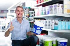 选择油漆的微笑的人顾客在大型超级市场用桶提 库存图片