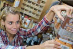 选择油漆的愉快的少妇顾客在家庭用品大型超级市场 免版税图库摄影
