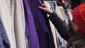 选择温暖的毛线衣在服装店的玻璃和红色被编织的帽子的妇女 影视素材