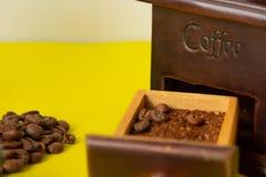 选择焦点在葡萄酒木磨咖啡器的咖啡豆在黄色背景 免版税库存照片