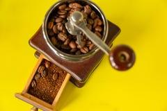 选择焦点在葡萄酒木磨咖啡器的咖啡豆在黄色背景 库存照片