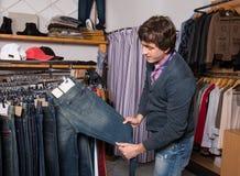 选择牛仔裤的英俊的人在购物期间 免版税库存图片