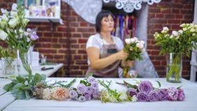 选择玫瑰色branche的Defocused专业卖花人为花的布置在花卉设计演播室 免版税库存图片