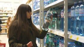 选择瓶矿泉水的美丽的妇女在超级市场 采取从架子的女孩产品在杂货 股票录像
