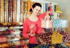 选择甜点的女孩在商店 免版税库存图片