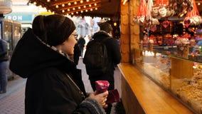 选择甜点的快乐的女性在圣诞节市场摊位在英国 免版税库存图片