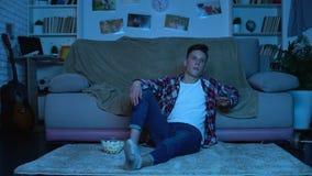选择电视频道的乏味少年吃玉米花和浪费时间,终日懒散在家的人 股票录像